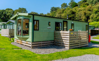 holiday caravan with large window and small wooden balcony