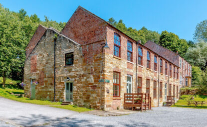 exterior of large old brick and stone building set in a sunny clearing of woodland
