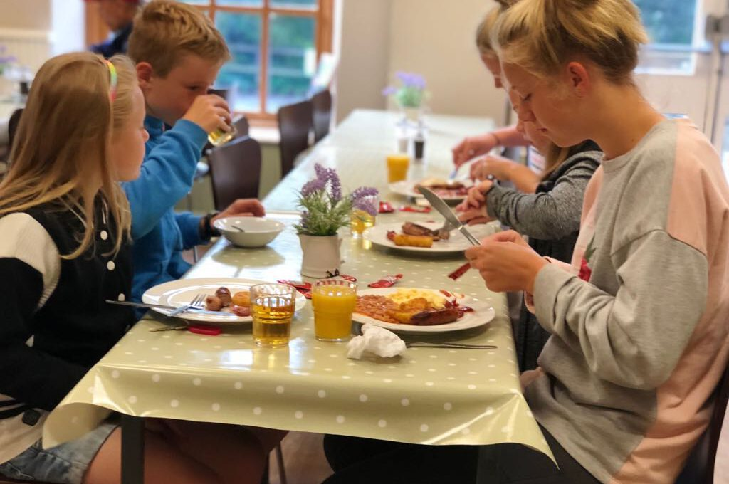 family sat at cafe table eating a cooked breakfast