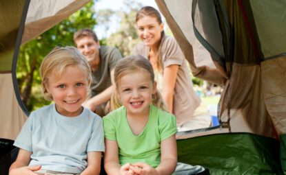 couple with two young children happily camping in tent
