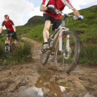 two cyclists on mountain bikes on muddy nature trail
