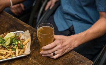 man holding pint of beer with food on the table