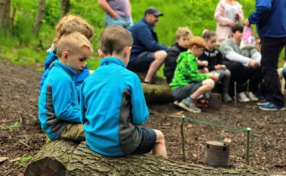 group of childrens sitting on logs in woodland learning bushcraft skills