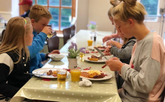 family with children eating a cooked english breakfast in Cote Ghyll Mill dining room