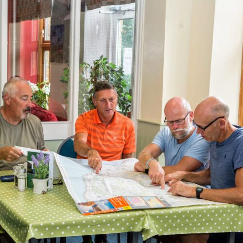 4 men looking at map whilst sat at dining table in Cote Ghyll Mill