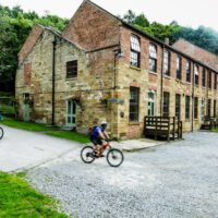 cyclist riding into Cote Ghyll Mill carpark