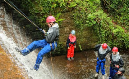 man abseiling down the old mill waterfall