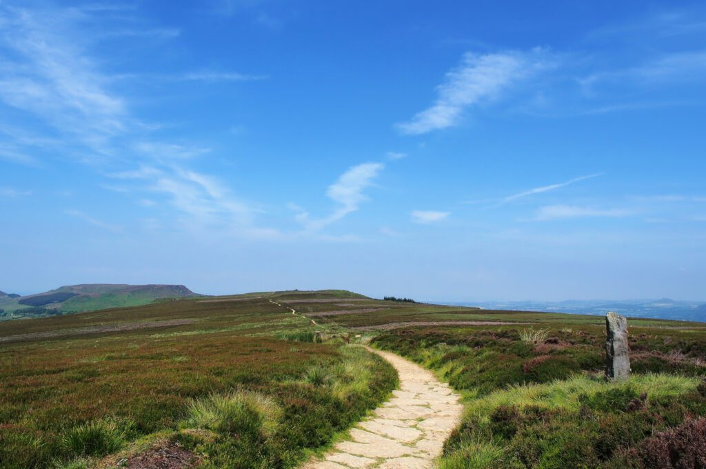 small winding moorland footpath beneath bright blue sky