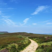 small winding moorland footpath beneath bright blue sky