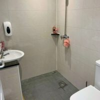 fully tiled shower room with sink and toilet