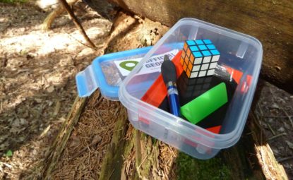 Tupperware box filled with small trinkets sitting open on log in woodland