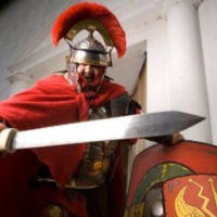 Man dressed as roman centurion with sword and shield