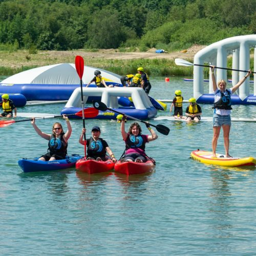 Huge inflatable obstacle course in middle of lake, with people canoing and paddle boarding nearby